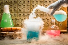 University chemical lab during experiment with periodic table of elements. On old wooden table stock image