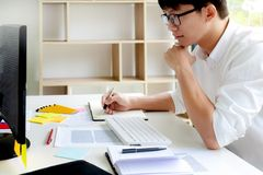 University / college student doing homework in classroom, education concept.  royalty free stock photography