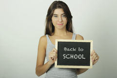 University college student holding a chalkboard saying back to s Stock Photography