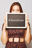University college student holding a chalkboard saying education Royalty Free Stock Images