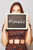 University college student holding a chalkboard saying finals Stock Photos