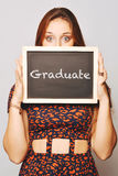 University college student holding a chalkboard saying graduate Royalty Free Stock Photos