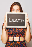 University college student holding a chalkboard saying learn Royalty Free Stock Photos