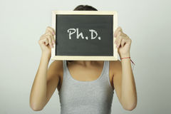 University college student holding a chalkboard saying Ph.D. Royalty Free Stock Photo