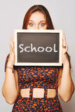University college student holding a chalkboard saying school Stock Photography