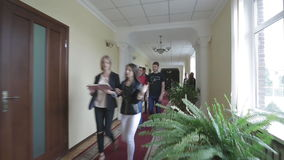 University Or College Students Chatting In The Hallway. VINNITSA, UKRAINE - MAY 2016: Students walking in the hall together at the university stock video footage