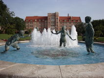 University Dormitory. This is a water fountain that has bronze statues of people playing and having fun. There is a university dormitory in the back ground with stock photos