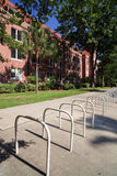 University Dormitory Bike Stands. Portrait view of a red brick university campus dormitory with bicycle stands in the foreground on a clear blue sky day royalty free stock images