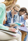 University female student with friends studying together in park Stock Photography