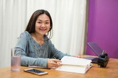 University female Student read book for exam. Portrait of University female Student in house read text book and write or take note on working table near computer royalty free stock image