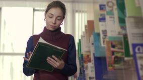 University girl choosing a suitable book in library archive stock footage