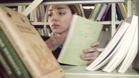 University girl looking for a suitable book in library. University girl looking for a suitable book on bookcase in library. Close-up shot stock footage