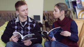 University girl and university boy sitting in library and discussing their books stock video
