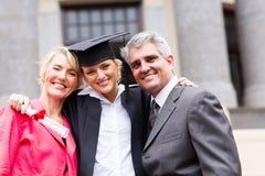 University graduate parents. Portrait of happy female university graduate and parents at ceremony Stock Photos