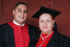 University graduate in robes with his grandmother. royalty free stock image