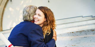 University Graduation Certificate Hugging Success Concept stock images