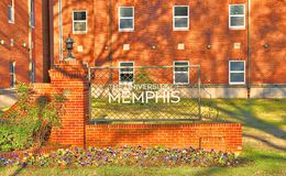 University of Memphis Entrance Sign Surrounded by Flowers. Marker entrance sign at the University of Memphis in Memphis, Tennessee Stock Image