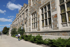 University of Michigan. A student walks behind the stone gothic style building of the Law School, one of the most highly rated in the United States Royalty Free Stock Images