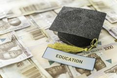 University Mortarboard academic cap on Nigerian Naira notes. Savings for education stock images