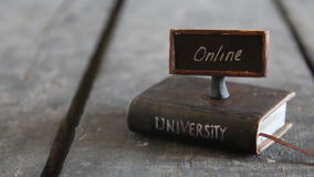 University online degrees idea. Book - computer and inscription university, vintage style stock video footage