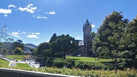 University of Otago Campus Dunedin. The old university clocktower watching over the Leith river, and the green trees and lawns of the Otago University, in stock images