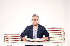 University professor. Portrait of middle-aged professor sitting at desk with book heaps on it stock photos