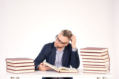 University professor. Portrait of middle-aged professor sitting at desk with book heaps on it stock image