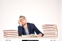 University professor. Portrait of middle-aged professor sitting at desk with book heaps on it stock photography