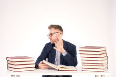 University professor. Portrait of middle-aged professor sitting at desk with book heaps on it royalty free stock photography