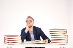 University professor. Portrait of middle-aged professor sitting at desk with book heaps on it royalty free stock images