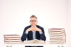 University professor. Portrait of middle-aged professor sitting at desk with book heaps on it stock photo