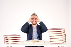 University professor. Portrait of middle-aged professor sitting at desk with book heaps on it stock images