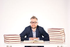 University professor. Portrait of middle-aged professor sitting at desk with book heaps on it royalty free stock photo