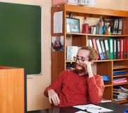 University Professor Sit At Desk In Classroom Listen To Report. High School Education Stock Photography