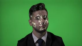 University professor using augmented reality having mathematic hologram formula projected on his face on green screen background -. Young male university stock video footage