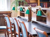 University or school library interior. Desks with green lamps, bookshelfs royalty free stock images