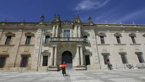 University of Seville. Tourist woman waving spanish flag at University of Seville, dates to the 15th century, under the name of Colegio Santa Maria de Jesus, in stock video footage