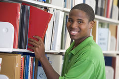 University student choosing book in library. Male student selecting book in library royalty free stock photography