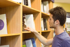 University student choosing books on bookshelves Royalty Free Stock Photography