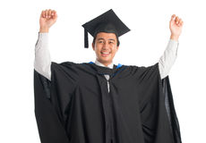 University student graduating. Attractive Southeast Asian male university student in graduation gown arms raised celebrating success, standing isolated on white Stock Photo