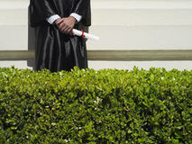 University student in graduation gown holding diploma, mid-section, hedge in foreground Royalty Free Stock Photos