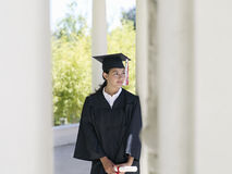 University student in graduation gown and mortar board holding diploma, smiling royalty free stock photos