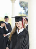 University student in graduation gown and mortar board, smiling, portrait, focus on foreground Stock Images
