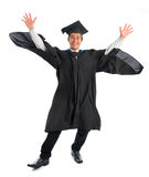 University student graduation jumping. Full body excited Asian male university student in graduation gown jumping high, isolated on white background. Good Stock Images
