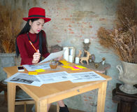 University student of Interior Design doing homeworks, reviewing. Housing project and completing project. The girl contemplates her blueprint Royalty Free Stock Photography