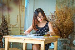 University student of Interior Design doing homeworks, reviewing. Housing project and completing project. The girl contemplates her blueprint Royalty Free Stock Photos