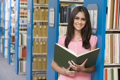 University student in library. University student studying in library holding book stock images