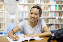 University student in library. Attractive african american university student sitting in library stock photography