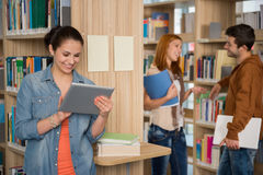 University student looking at tablet in library. University student looking at tablet with classmates talking in library Stock Photos