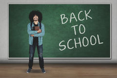 University student looks confident in classroom. University student looks confident while holding a book with back to school word on board in the classroom Stock Photo